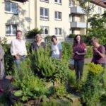 Die Damen von der WoGe mit der Besuchergruppe im Garten